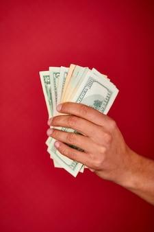 Man's hand hält und zeigt dollar-banknotengeld isoliert auf rotem hintergrund, innen-, studioaufnahme, kopienraum
