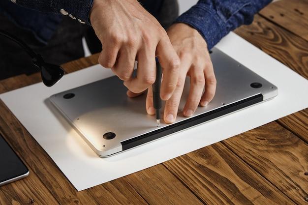 Man schließt das obergehäuse eines metallischen, schlanken laptops, um es wieder zusammenzubauen, nachdem er in seinem labor repariert, gereinigt und repariert wurde