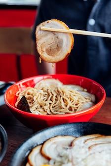 Man schnappt sich chashu-schweinefleisch aus der schüssel mit essstäbchen von shoyu chashu ramen an seiner hand.