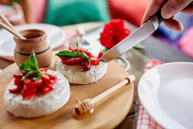 Man schnitt gegrillten camembertkäse mit erdbeer-, honig- und basilikumblättern, delikatessen