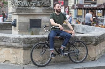 Man sitzt mit seinem Fahrrad