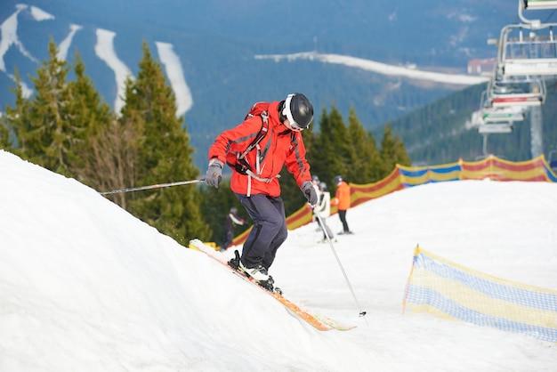 Man skifahrer skifahren auf der schneebedeckten piste im skigebiet in den bergen. wälder, skipisten und skilift im hintergrund. skisaison und wintersportkonzept