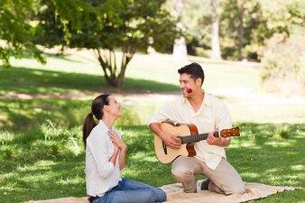 Man spielt Gitarre für seine Freundin