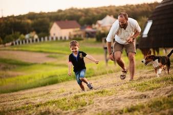 Man spielt mit seinem Sohn und einem Hund auf dem Feld