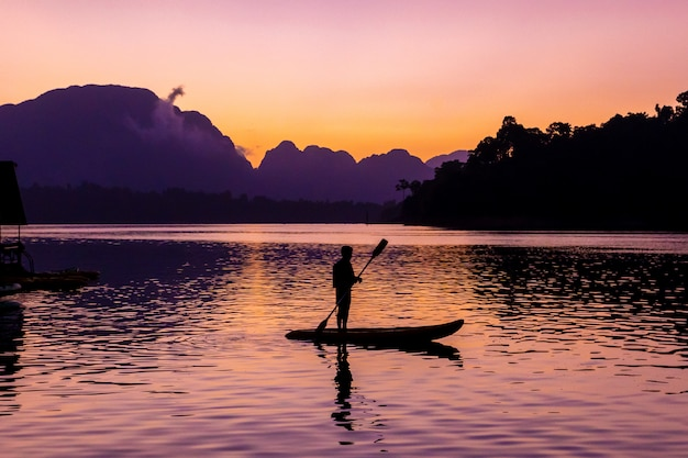 Man steht beim sonnenaufgang auf seinem kajak am ratchaprapa-damm oder bekannt als cheow lan-damm