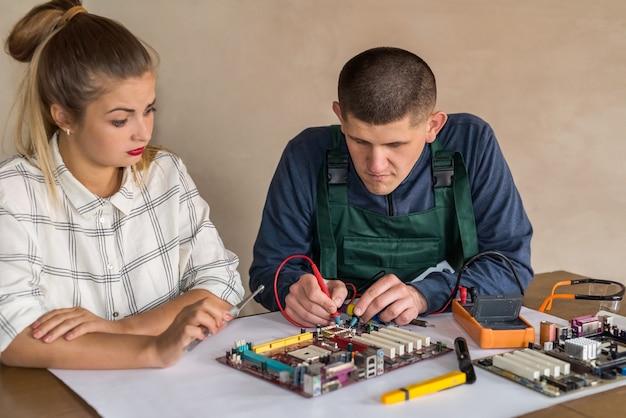 Man testet motherboard des personalcomputers durch multimeter