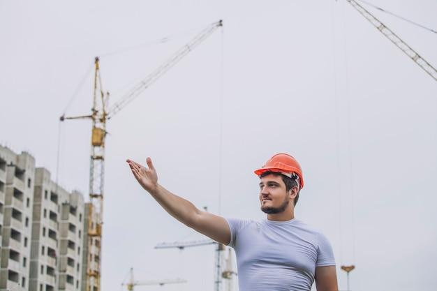 Man the builder arbeitet als vorarbeiter im helm, um die sicherheit auf der baustelle zu gewährleisten. arbeiter, ingenieur, vorarbeiter, architekt.