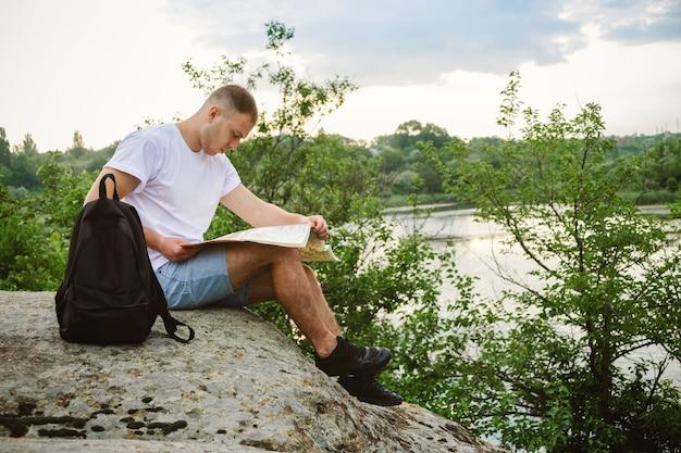Man tourist, der auf einem stein am fluss sitzt, las die karte.