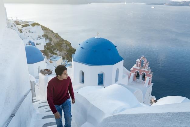 Man tourist, der weiß getünchte dörfliche blaue kuppeln im mittelmeer von oia santorini griechenland besucht