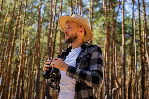 Man tourist in einem hut und einem karierten hemd schaut durch fernglas im wald.
