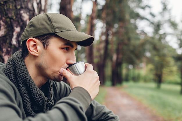Man tourist reisender trinkt heißen tee von thermoskanne tasse im frühlingswald. camping, reisen, wandern und sportkonzept