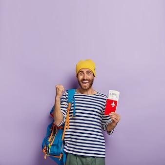 Man tourist trägt rucksack, zeigt reisepass mit flugtickets