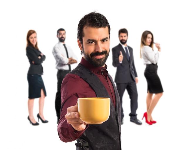 Man trägt eine weste mit einer tasse kaffee