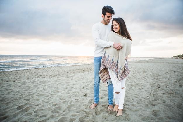 Man umarmt seine freundin am strand