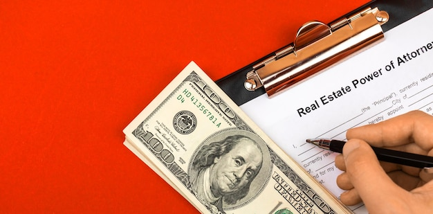Man unterschreibt und füllt ein vollmachtsformular für immobilien aus. schreibtisch und zwischenablage nach absprache. foto von oben