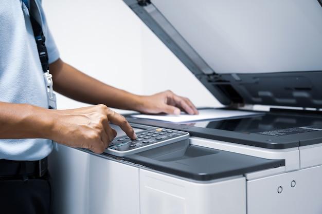 Man worker drücken sie die starttaste am kopierer, um den fotokopierer zu verwenden.