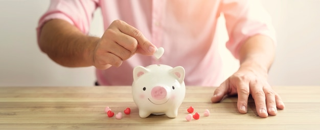 Manâ € ™ s hand legt das herz in das sparschwein. das konzept des blutspenders oder der rettung von leben