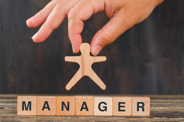 Managementkonzept mit holzwürfeln auf holztischseitenansicht. hand hält menschliches modell.