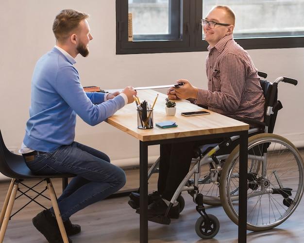 Manager arbeitet mit behinderten arbeitnehmern zusammen