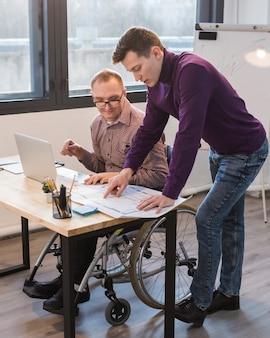 Manager arbeitet mit behinderten mann zusammen