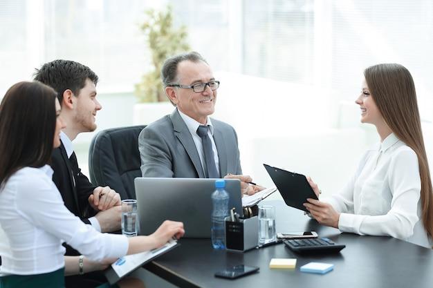 Manager bespricht arbeitsprobleme mit seinen assistenten hinter einem schreibtisch