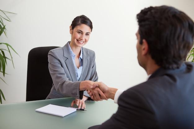 Manager, der die hand eines kunden rüttelt