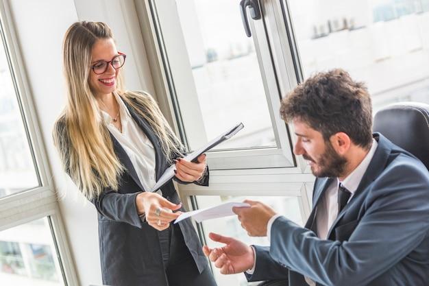 Manager, der ihrem weiblichen sekretär dokument im büro gibt