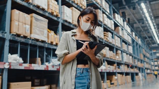Manager der jungen asiatischen geschäftsfrau, der gesichtsmaskenlager unter verwendung des inventars der digitalen tablette prüft trägt