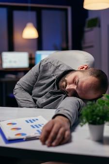 Manager, der wegen überarbeitung am arbeitsplatz ein nickerchen macht. workaholic-mitarbeiter schläft ein, weil er spät nachts allein im büro für ein wichtiges unternehmensprojekt arbeitet.