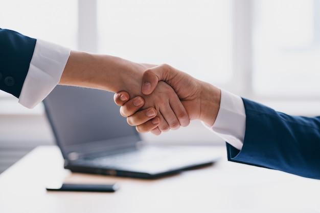 Manager, die sich die hände schütteln, sind erfolgreiche büro-laptop-profis