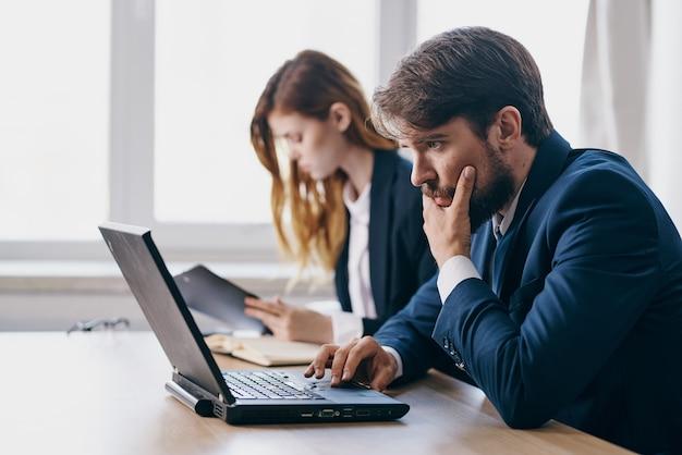 Manager, die vor einem laptop sitzen, arbeiten internet-profis zusammen