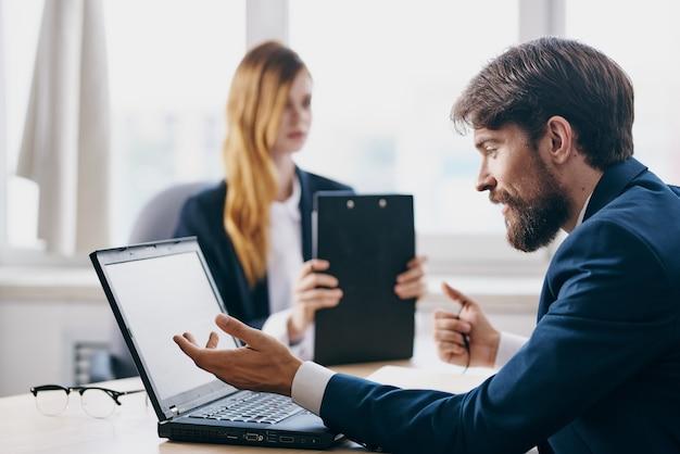 Manager, die vor einem laptop sitzen, arbeiten internettechnologien zusammen