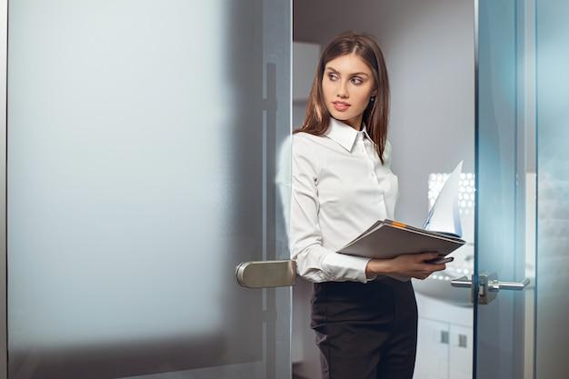 Manager frau stehen im büro bei der arbeit und hält dateien clip-dokumente, während zur seite schauen.