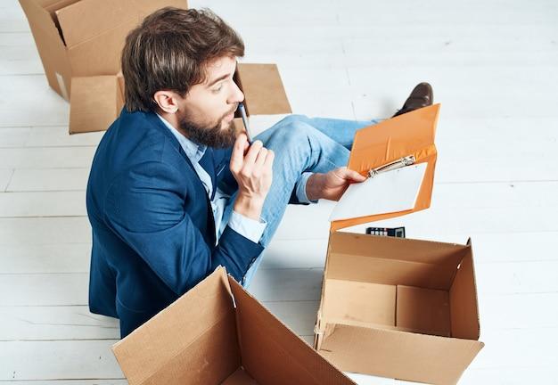 Manager im anzug mit kartons mit sachen, die an einen neuen arbeitsplatz ziehen. foto in hoher qualität