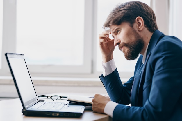 Manager im büro am schreibtisch vor einem laptop karrieretechnologien