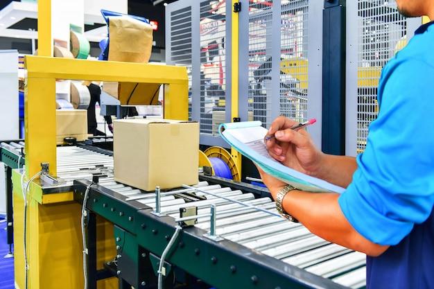 Manager ingenieur, der pappkartons auf förderband im distributionslager überprüft.