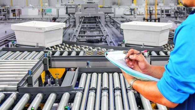 Manager-ingenieur, der plastikboxen auf dem förderband überprüft