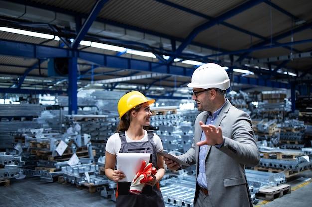Manager mit helm und industriearbeiter diskutieren über die produktion in der metallfabrik