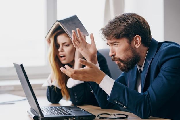 Manager sitzen an einem schreibtisch mit einem laptop kommunikationsbeamte