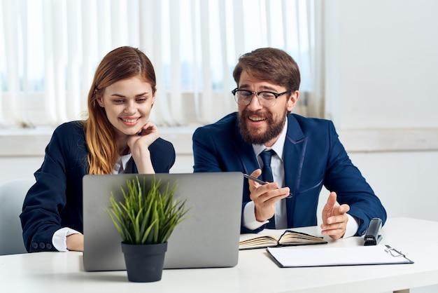 Manager sitzen an einem schreibtisch vor einer laptop-technologie