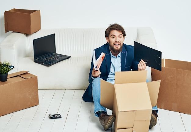 Manager sitzt auf dem boden mit kartons, die dinge verpacken