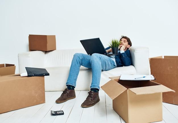 Manager sitzt auf der couch mit einem laptop, der dinge im büro auspackt