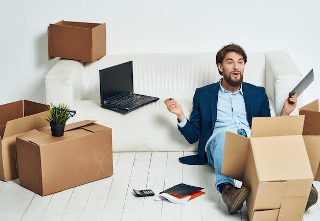 Manager sitzt auf einer weißen couchbox mit sachen, die sich professionell bewegen