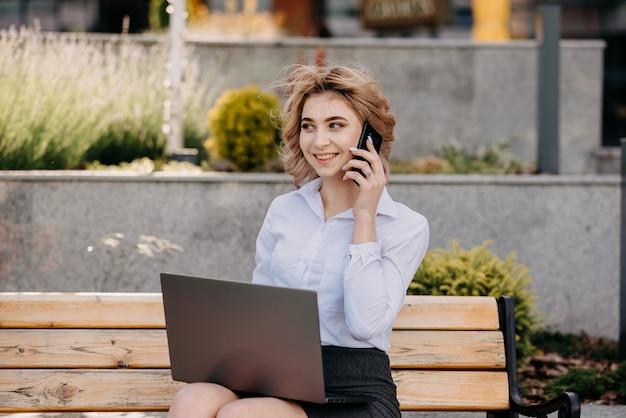 Manager sitzt außerhalb von gebäuden. büroangestellter telefoniert mit laptop