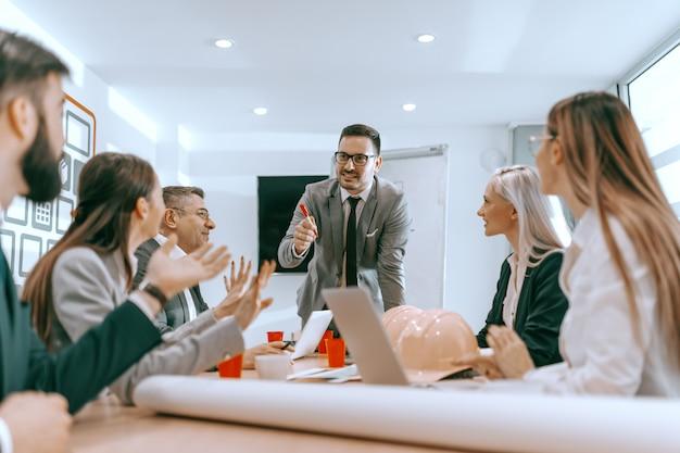 Manager steht und spricht mit mitarbeitern im sitzungssaal. geschäftskonzept des architekten. in der vereinigung liegt stärke.