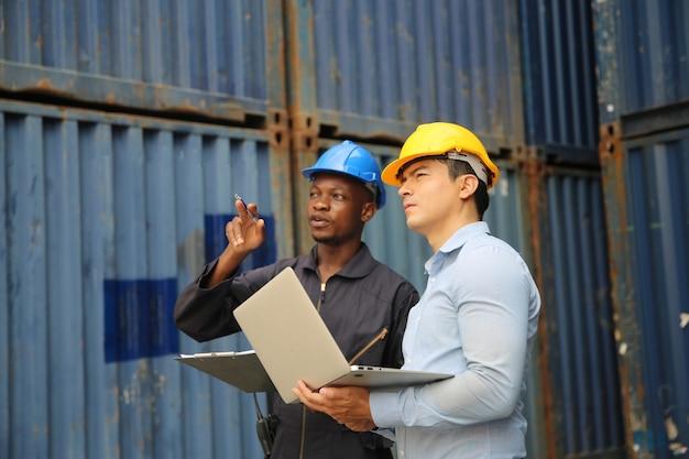 Manager und hafenarbeiter, die über das dokument des dockcontainer-versandlagers diskutiert werden, tragen einen schutzhelm, eine gesichtsmaske und eine funkverbindung.