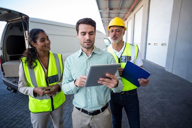 Manager und lagerarbeiter diskutieren mit digitalem tablet