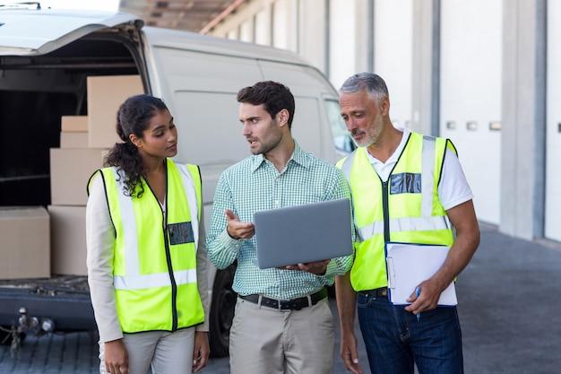 Manager und lagerarbeiter diskutieren mit laptop