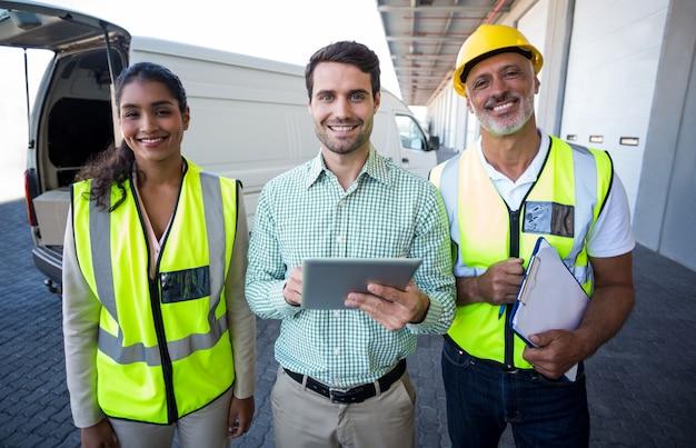 Manager und lagerarbeiter stehen mit digitalem tablet und zwischenablage