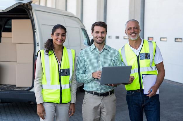 Manager und lagerarbeiter stehen mit laptop und zwischenablage